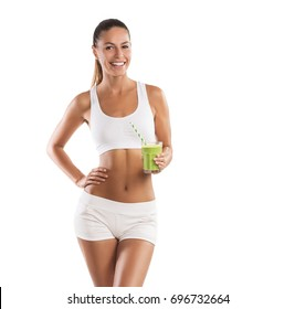 Fit, beautiful, young woman holding a healthy, green smoothie, isolated on white background