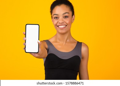 Fit Black Girl Showing Phone Blank Screen Standing Over Yellow Studio Background. Workout App Concept. Mockup, Selective Focus