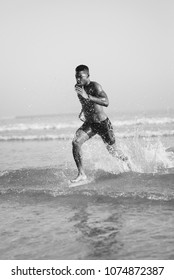 Fit black man running at seaside splashing watter. Black runner training legs power sprinting at the beach. Summer healthy lifestyle and sport motivation concept.