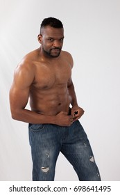 Fit Black man standing shirtless and showing off his muscular torso
