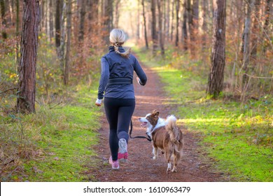 Fit blond woman jogging with her pet dog along a forest track in a rear view in a healthy active lifestyle concept