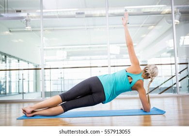 Fit blonde doing exercise on mat in fitness studio