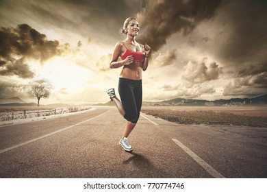 fit blonde girl jogging in the countryside in the sunset