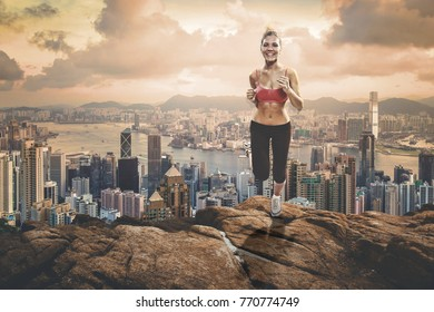 Fit blonde girl jogging up to the rocks hill over the metropolis