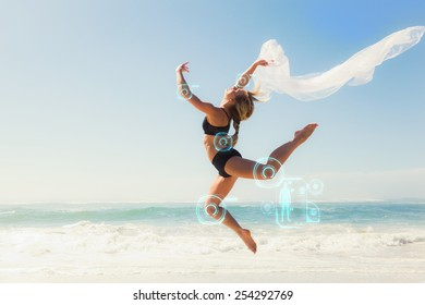 Fit blonde jumping gracefully with scarf on the beach against fitness interface