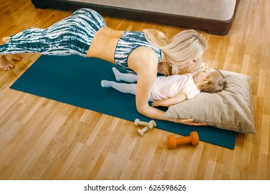 Fit blonde mother doing yoga fitness exercises in her home while her baby sleeping on the pillow. Toned image.