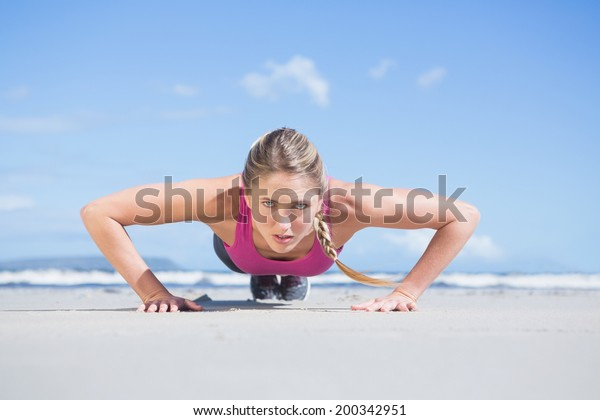 Fit blonde in plank position on the beach on a sunny day