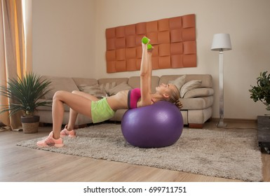 fit blonde woman in sportswear lifting dumbbells on fit-ball indoor at home interior