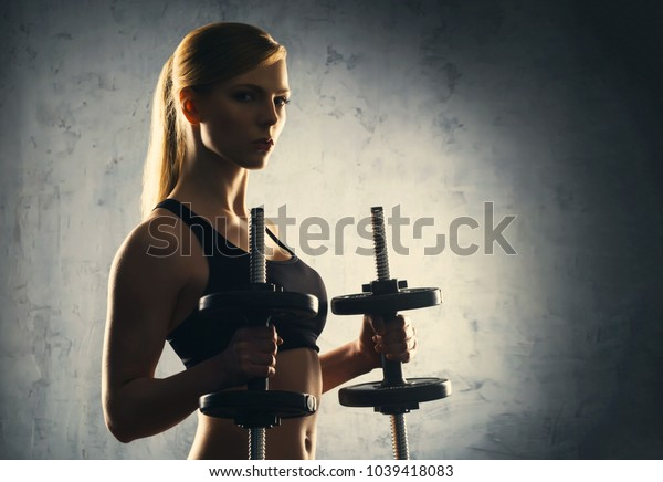 Fit body of beautiful, healthy and sporty woman with a dumbbells. Slim woman posing in sportswear.