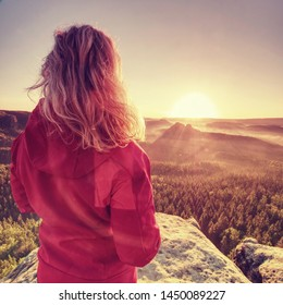 Fit body blond hair woman on the top of the high rocky mountain in the evening. Beautiful sunset autumn forests rocks and hills on the background