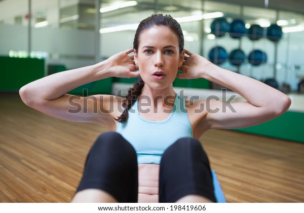 Fit brunette doing sit ups in fitness studio at the gym