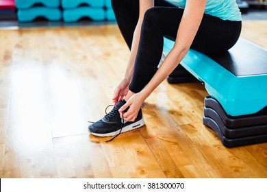 Fit Brunette Girl with Black Shoes, Black Legging and Blue and Yellow Sports Outfit and Shirt at the Gym working on her Fitness