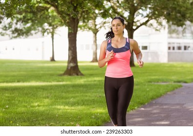 Fit brunette jogging in the park on a sunny day