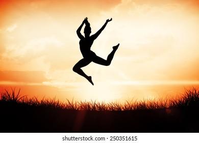 Fit brunette jumping and posing against orange sunrise