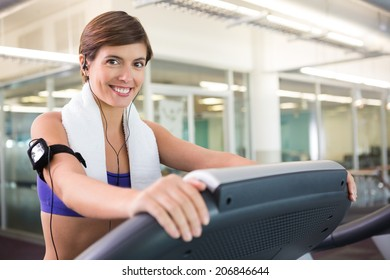 Fit brunette running on the treadmill listening to music at the gym