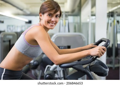 Fit brunette working out on the exercise bike at the gym