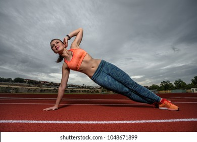 Fit brunette young female with fit athletic body performing one handed side plank pose on running field.