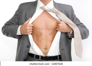 fit for business - young businessman dressed in suit, shirt and tie pulling his shirt open revealing well-built torso