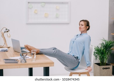 fit businesswoman standing on hands on chair at workplace