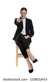fit businesswoman wearing black suit sitting and pointing forward against white studio background