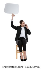 fit businesswoman wearing black suit sitting and holding speech bubble overhead while talking on phone and looking aside happy against white studio background