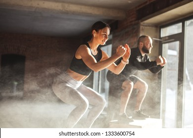 Fit caucasian couple doing squats on boxes in a crossfit style gym, well lit by bright sunlight.