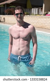 Fit Caucasian man with defined abs standing in an outdoor swimming pool in blue swimming trunks and aviator sunglasses.  Sexy man outside in pool, fitness model. Cute guy swimming.