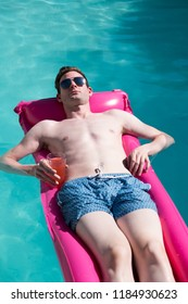 Fit Caucasian man in sunglasses floating on a pink raft in a swimming pool holding a drink. Man on holiday, enjoying the sun in an outdoor swimming pool, nice blue water, thin, good looking young man
