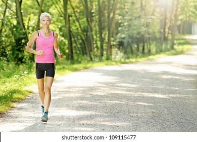 Fit caucasian woman jogging  in nature