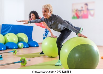 Fit Caucasian women doing crane exercise standing on one leg with their arms out to sides holding on to balance ball while training in fitness club