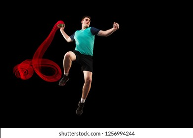The fit caucasian young male handball player at studio on black background. Fit athlete isolated on black with led light trail . The man in action, motion, movement. attack and defense concept