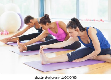 Fit class stretching legs on mats at yoga class in fitness studio