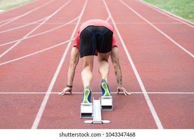 Fit and Confident Man in Starting Position Ready for Running