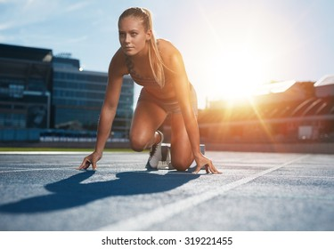 Fit and confident woman in starting position ready for running. Female athlete about to start a sprint looking away. Bright sunlight from behind.