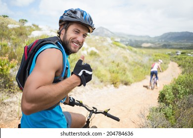 Fit couple cycling on mountain trail man smiling at camera on a sunny day