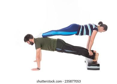 Fit couple doing push-ups - isolated on white