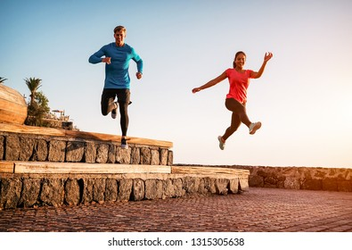 Fit couple doing workout running session at sunset outdoor - Sporty young people jogging next the beach - Healthy lifestyle and sport concept