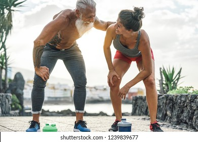Fit couple having a break after a fast race next the beach at sunset - Sporty people workout running outdoor - Fitness, wellness, sport, jogging and health lifestyle concept