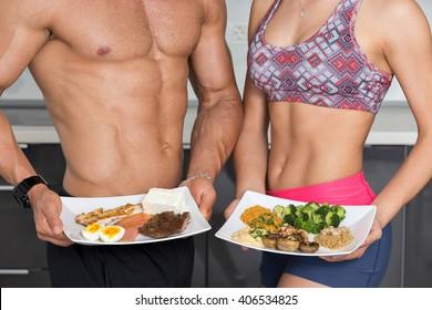 Pärchen in der Küche; Tier gegen Pflanzenproteine: ein Teller mit Rind-, Eier-, Lachs-, Käse- und Hühnergrill und ein anderer mit Nüssen, Pilzen, Broccoli, Lentil, Hummus und Quinoa