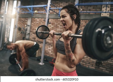 Fit couple lifting barbells in the gym