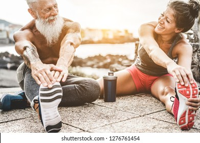 Fit couple making stretching before running workout - Joggers training outdoor at sunset together - Main focus on womaman face - Fitness, sport, wellness, workout, gym and healthy lifestyle concept
