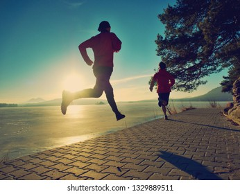 Fit couple, man and woman running along the waterfront. Sport motivation and healthy fitness lifestyle