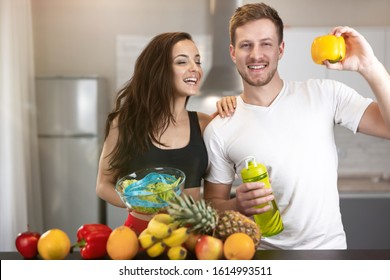 fit couple man and woman standing in the kitchen full of fruits and vegetables, he holds pepper, she holds bowl with salad, nutrition and dietology.