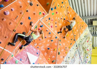 Fit couple rock climbing indoors at the gym