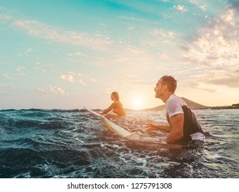 Fit couple surfing at sunset - Surfers friends having fun inside ocean - Extreme sport and vacation concept - Focus on man head
