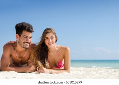 Fit couple taking sun at the beach