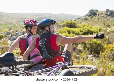 Fit cyclist couple sitting at the summit looking around on a sunny day