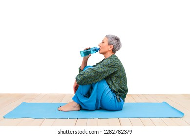 Fit eldery, adult woman in the studio. A woman drinks water, drinking in training, a healthy lifestyle of the elderly. Yoga classes fitness