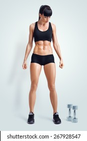 Fit female athlete in activewear ready to doing exercise with dumbbells. Strong abs showing. Image with clipping path.