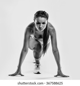 Fit female athlete ready to run over grey background. Female fitness model preparing for a sprint.